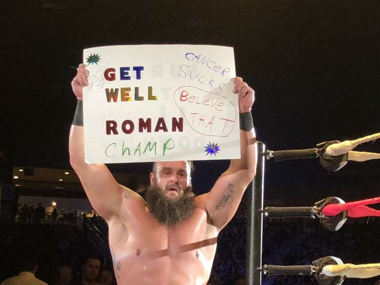 braun strowman holds up get well roman sign at wwe live event in